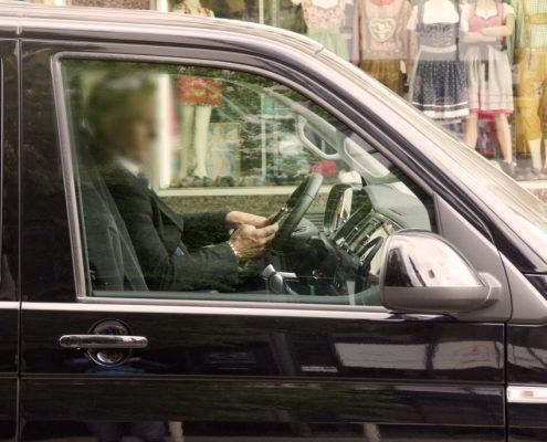 Ein Mann benutzt sein Handy am Steuer
