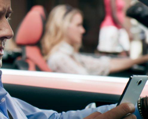 Ein Mann mit seinem Handy am Steuer, im Hintergrund eine Frau in ihrem Auto