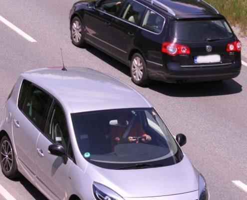 Ein silbernes und ein schwarzes Auto auf einer Straße