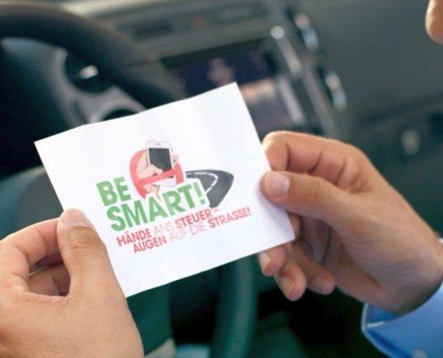 Mann hält Zettel mit BeSmart Logo