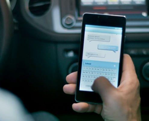 Hand tippt auf Smartphone am Steuer
