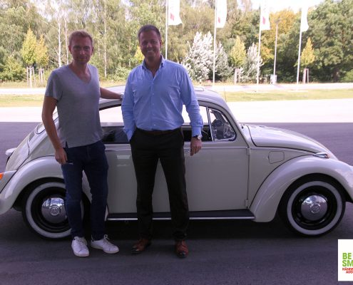 Michael Haberland und Christian Lindner lachen vor einem Käfer in die Kamera