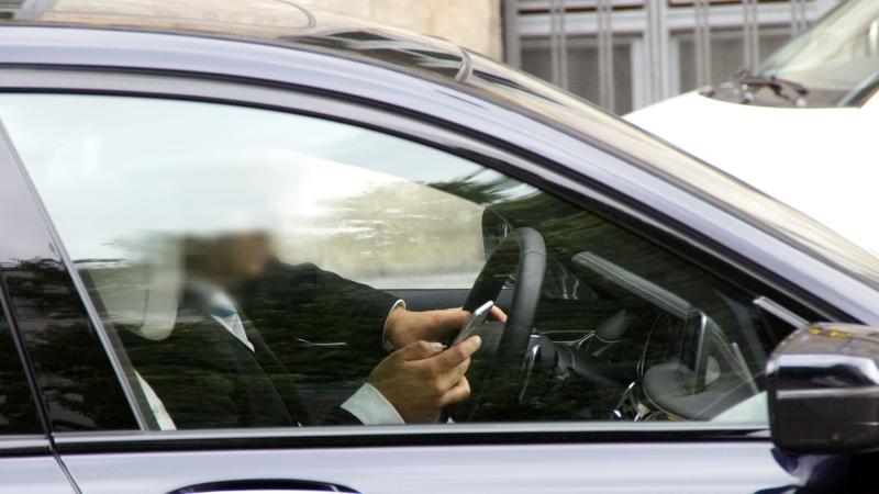 Ein Mann mit Handy am Steuer