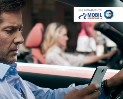 Mann mit Dreitagebart und blauem Hemd im Auto, linke Hand am Steuer, rechte Hand hält Smartphone. Im Hintergrund blonde Frau im Cabrio, Passanten.