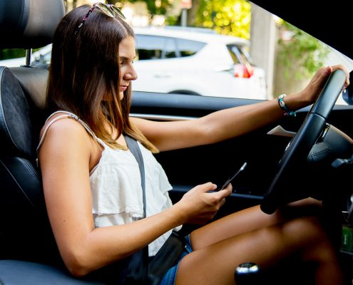 Junge Frau mit Sonnenbrille am Steuer eines Cabrios, eine Hand am Lenkrad, Smartphone in der anderen Hand.