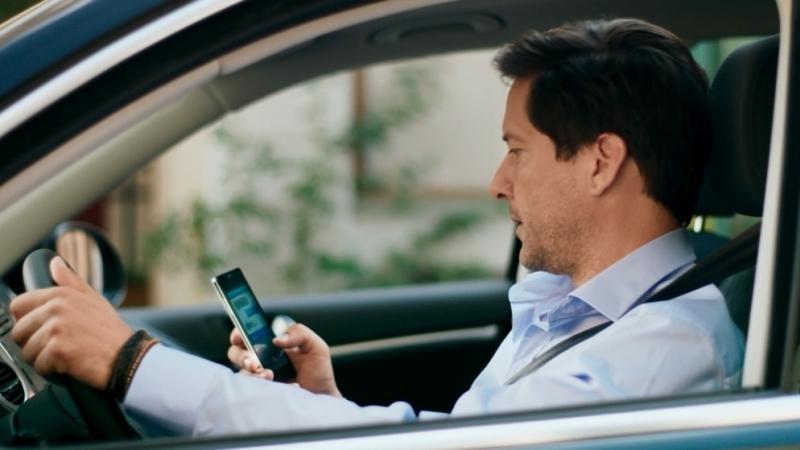 Ein Mann sitzt im Auto und spielt mit seinem Handy