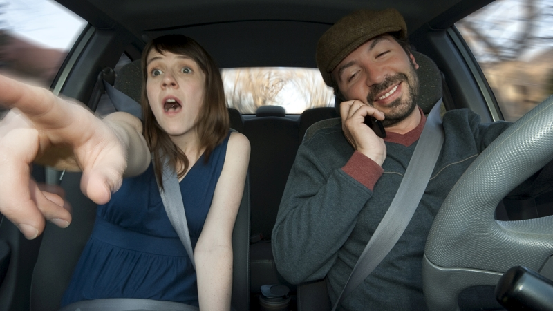 Ein Mann mit Handy am Steuer und eine Frau am Beifahrersitz, die erschrocken auf etwas zeigt