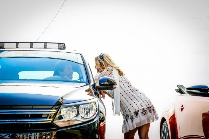 Ein im Auto sitzender Mann und eine blonde Frau auf der Straße sehen sich an