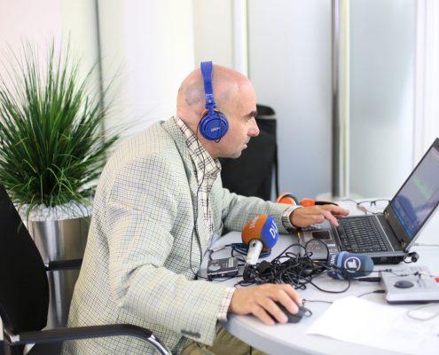 Mann mit Headset vor einem PC
