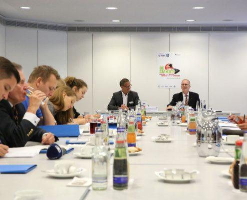 Konferenztisch mit Getränken, viele Personen am Tisch, 2 Wortführer am Tischende. Im Hintergrund Plakat der Kampagne Be Smart