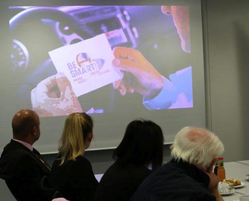 Vier Personen sehen sich einen Werbefilm auf der Leinwand an