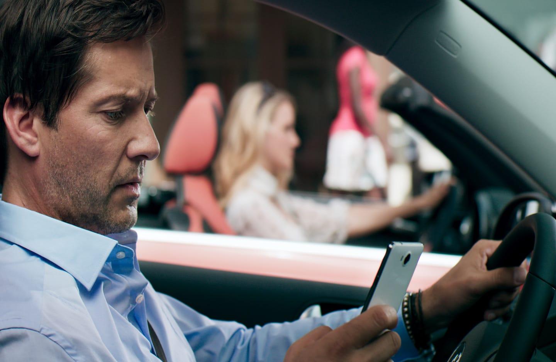 Mann mit Handy am Steuer