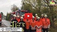 Eine Gruppe Feuerwehrleute steht vor einem Feuerwehrauto auf der Straße