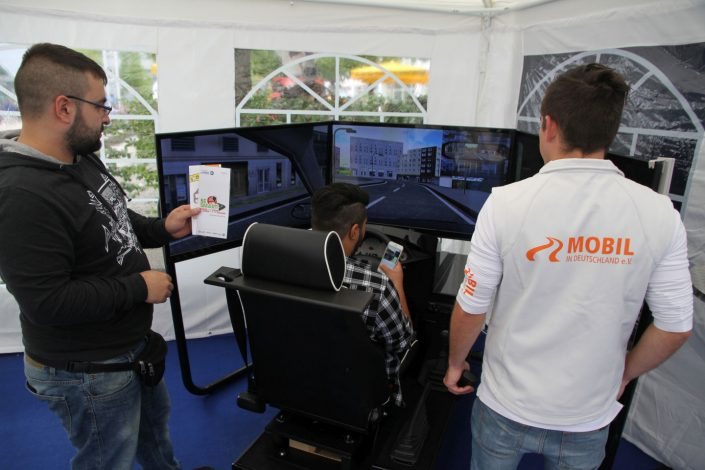 Drei Männer testen den Fahrsimulator