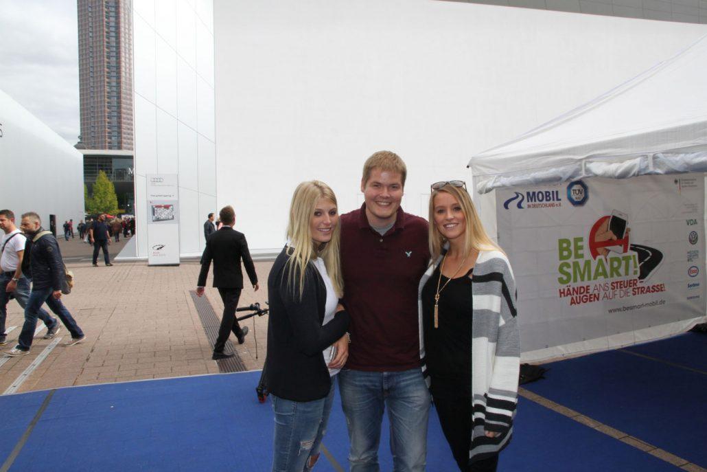 Zwei junge blonde Frauen mit einem jungen Herren in der Mitte