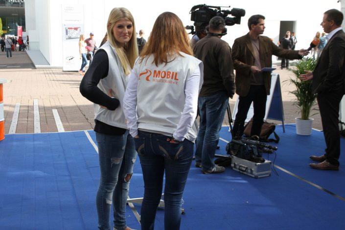 zwei Frauen im Vordergrund und Michael Haberland im Interview im Hintergrund