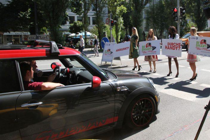 Vier Mädchen in Dirndl und Schildern in der Hand halten die Autos auf der Straße an