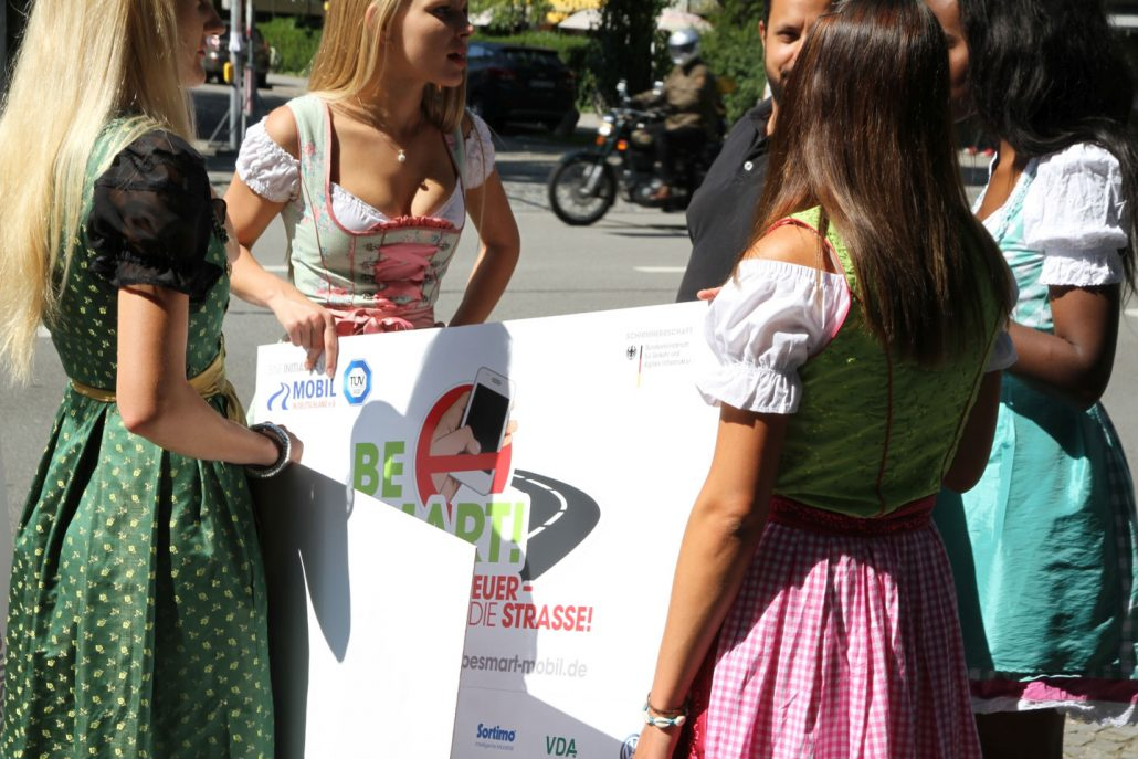 Vier Mädchen in Dirndl und Schildern in den Händen und ein Mann stehen vor einer belebten Straße im Kreis und reden