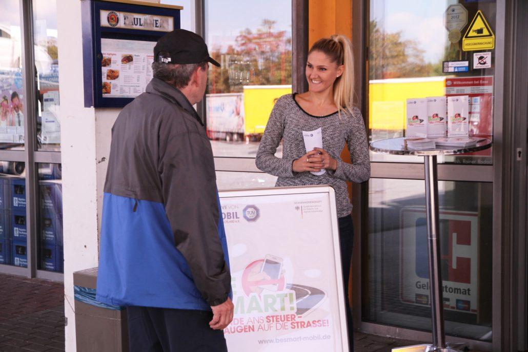 Eine blonde, junge Frau mit einem BeSmart-Informationsstand und Plakat vor einem Laden und redet mit einem älteren Herren