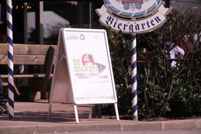 Ein Plakatehalter auf dem Bordstein vor einem Münchner Biergarten