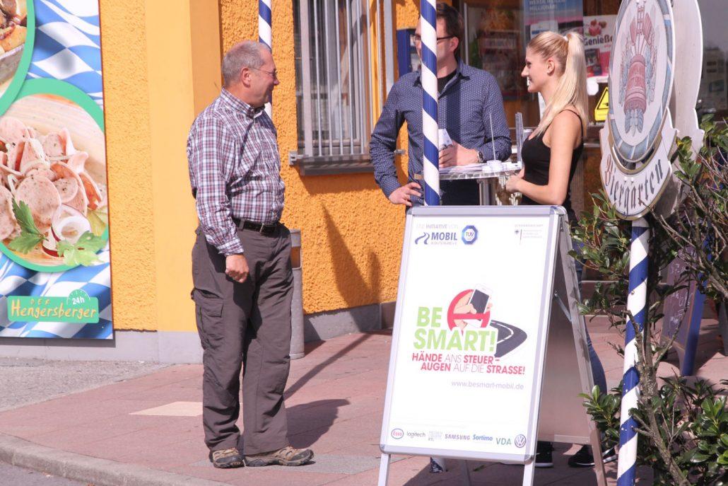 Ein Mann und eine Frau an einem Infostand sprechen mit einem interessierten älteren Herren. BeSmart Plakat im Vordergrund