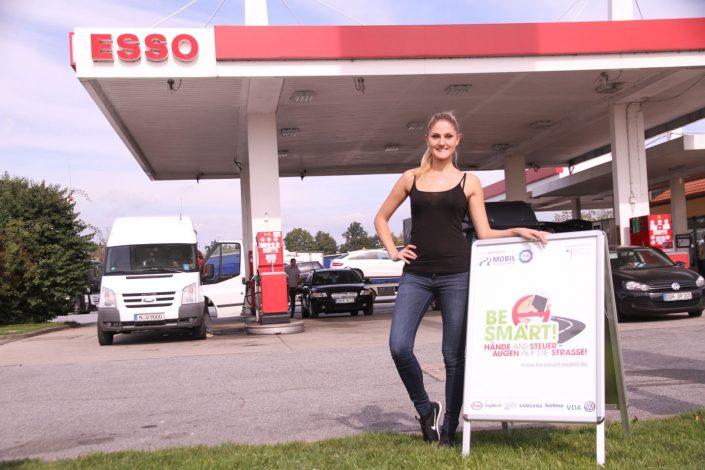 Blonde junge Frau mit BeSmart Plakat vor Esso-Tankstelle