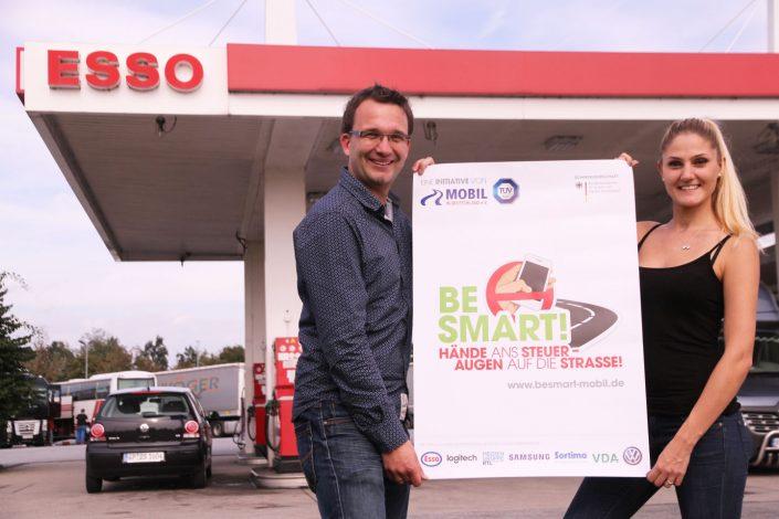 Ein Mann und eine Frau vor einer Esso-Tankstelle halten das BeSmart-Plakat in die Kamera