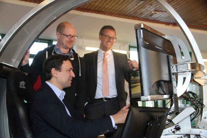 Georg Eisenreich fährt mit dem Fahrsimulator und Michael Haberland und ein weiterer Mann sehen zu