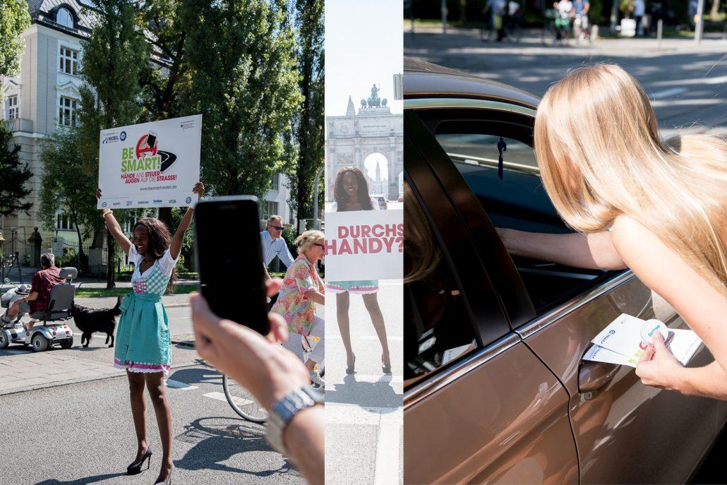 Mädchen in Dirndl verteilen BeSmart Werbeartikel und halten Schilder in die Luft