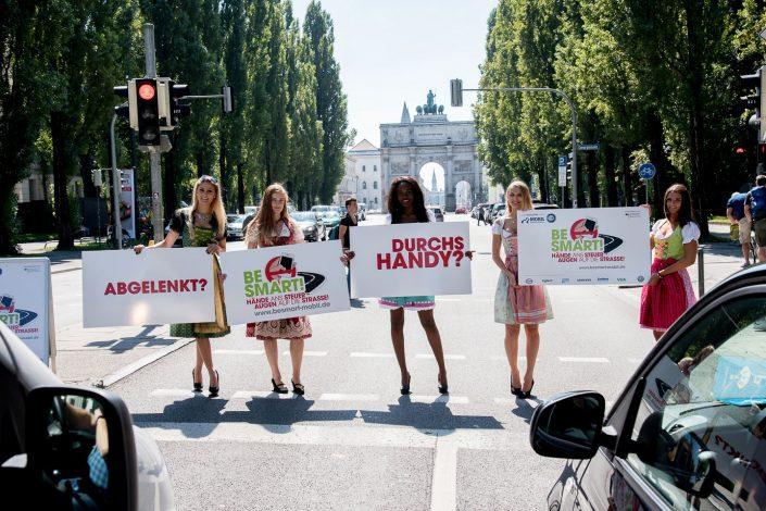 5 Mädchen in Dirndl halten auf einer Straße Schilder in den Händen