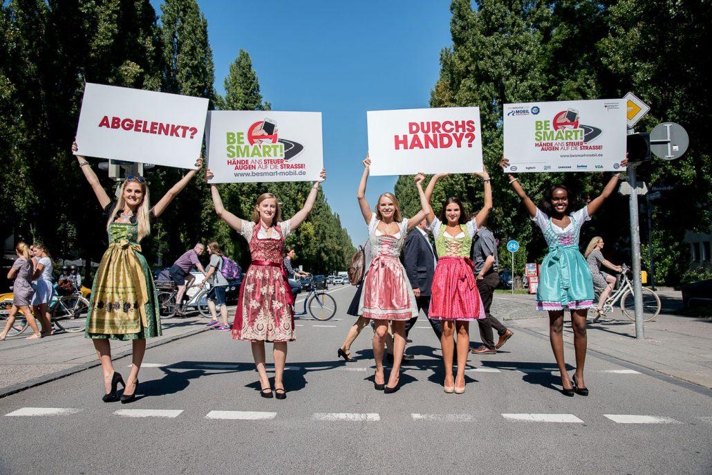 5 Mädchen in Dirndl halten auf einer Straße Schilder in die Luft