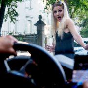 Ein Mann mit Handy am Steuer übersieht eine blonde Frau auf der Straße