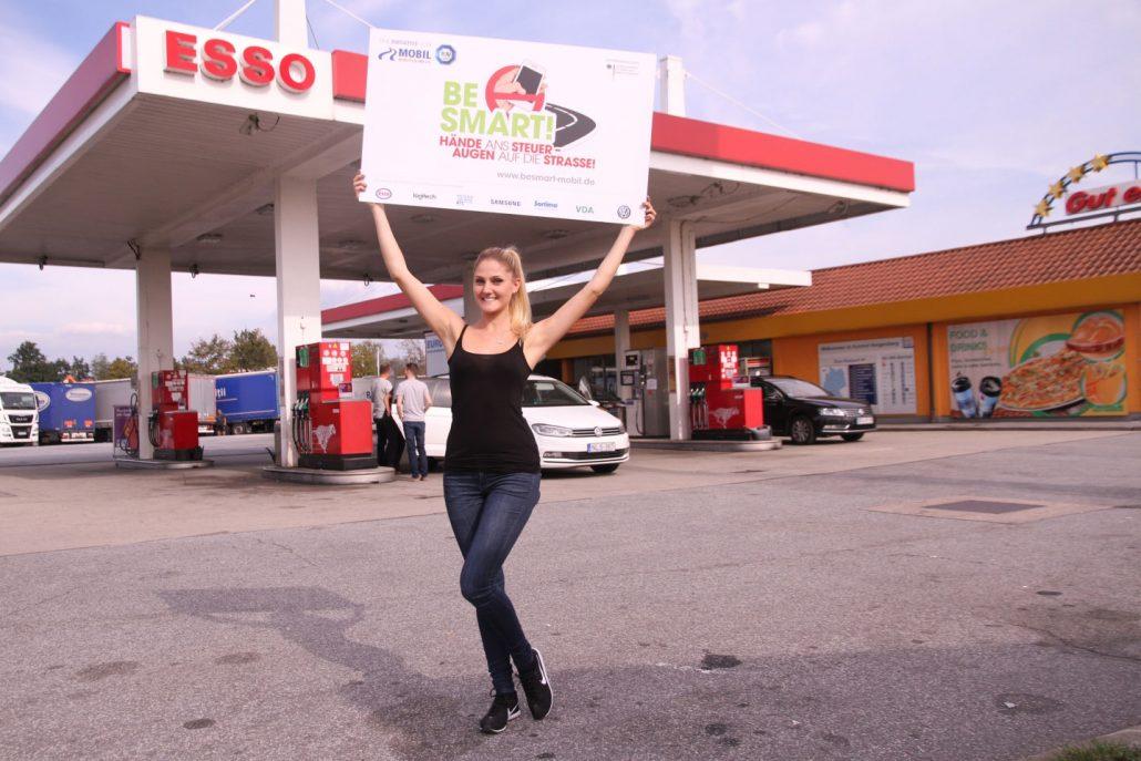 Junge blonde Frau vor ESSO-Tankstelle