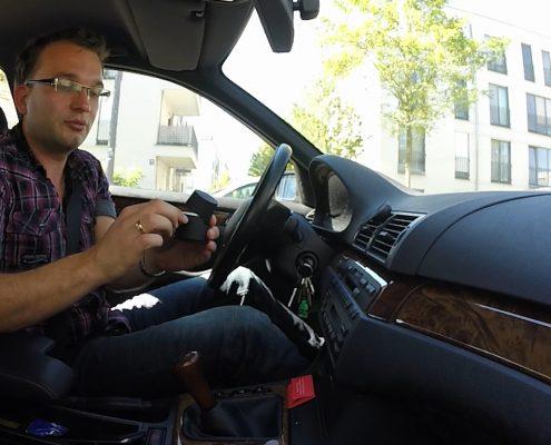 Mann errichtet in seinem Auto die Handyhalterung