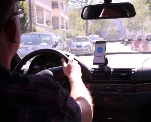 Mann in Auto mit Handyhalterung
