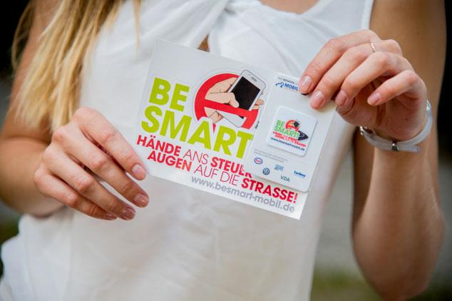 Junge Dame mit blonden Haaren hält Flyer und Karte von BE SMART in den Händen