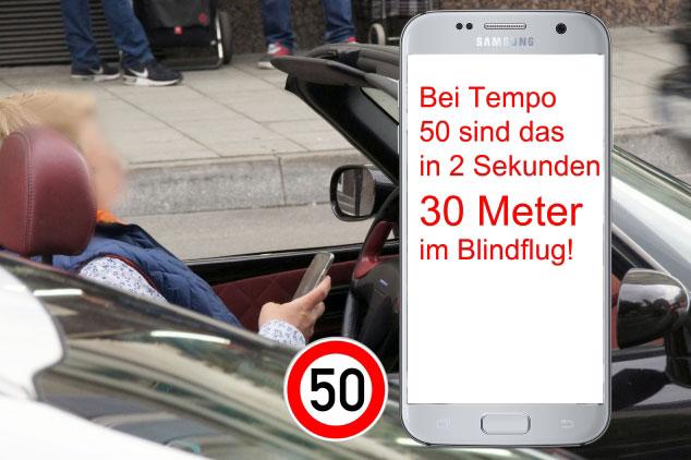 Person am Steuer eines Cabrios hält Smartphone in der Hand