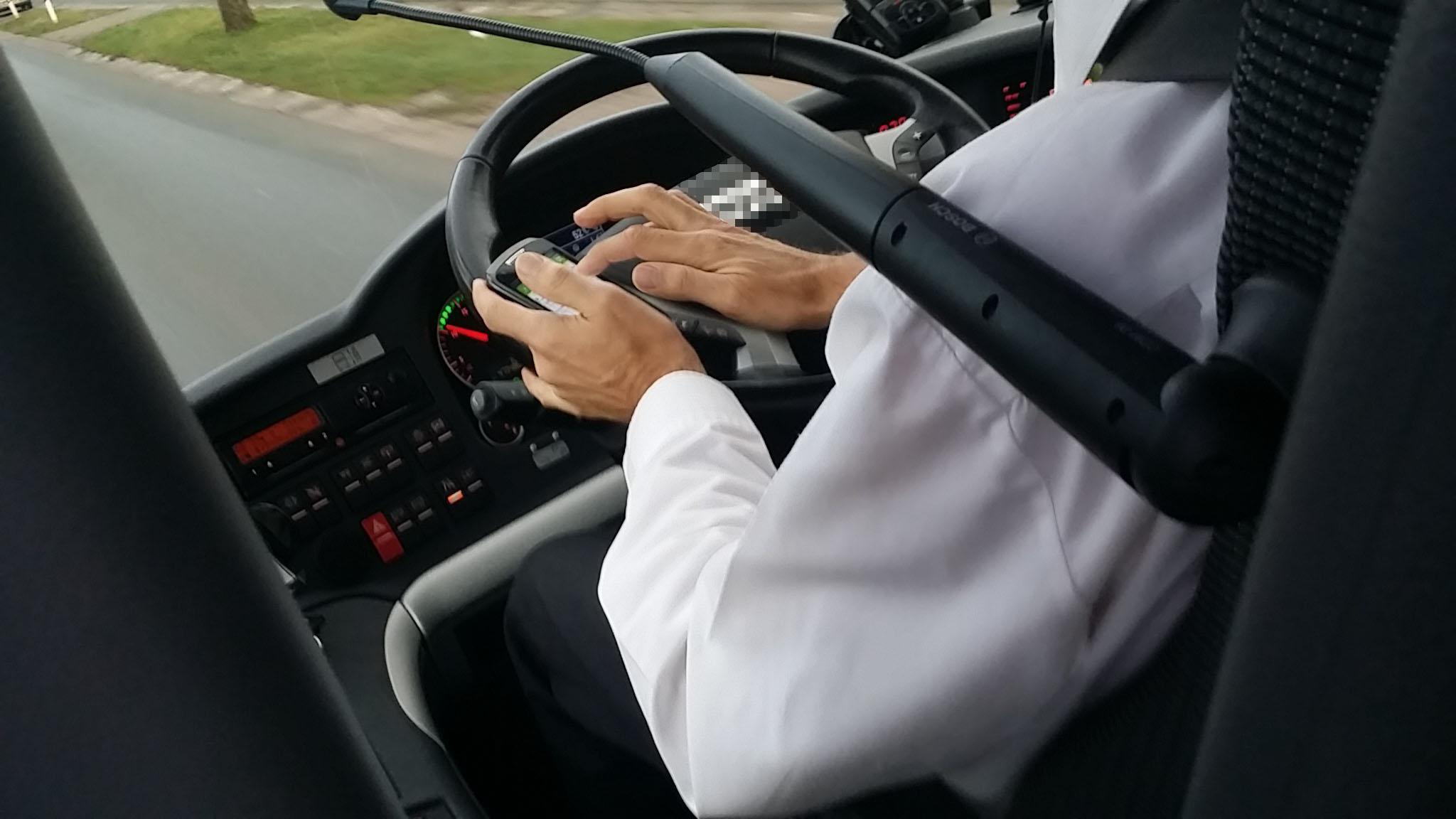 Mann am Steuer eines Linienbusses, tippt auf seinem Smartphone