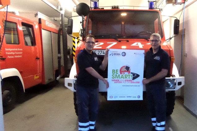 Zwei Feuerwehrmänner vor Dienstfahrzeug halten BE SMART Plakat in den Händen