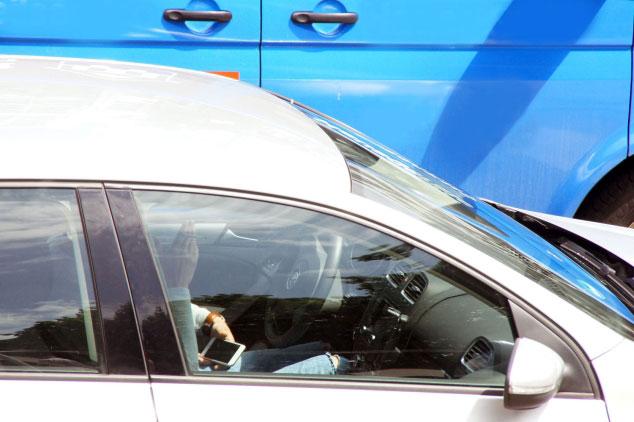 Person auf Fahrersitz im Auto blickt aufs Handy