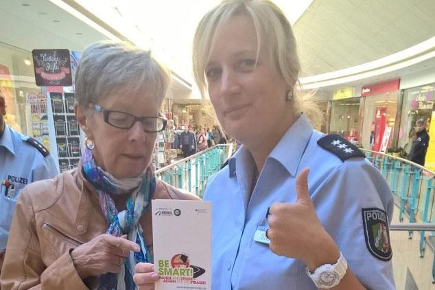 Ältere Dame und Polizistin in Einkaufszentrum mit BE SMART Flyer