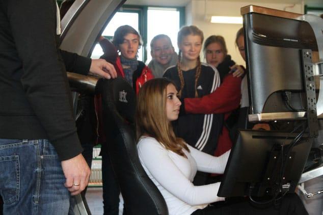 Mehrere Jugendliche stehen um Fahrsimulator herum während ein Mädchen fährt