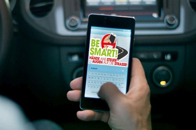 Person am Steuer eines Autos mit Smartphone in der Hand, auf dem Display Kampagnenlogo BeSmart sichtbar.