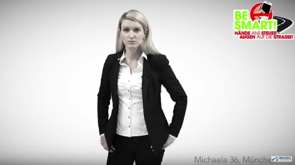 Blonde Frau in Hosenanzug und weißer Bluse vor grauem Hintergrund