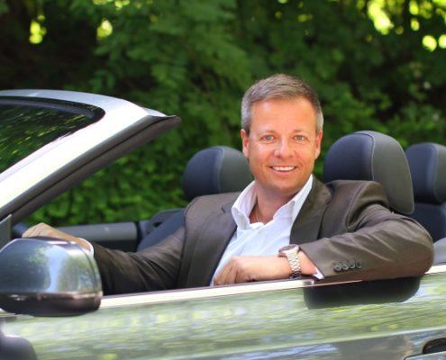 Mann in grauem Anzug und weißem Hemd in Cabrio vor Naturkulisse