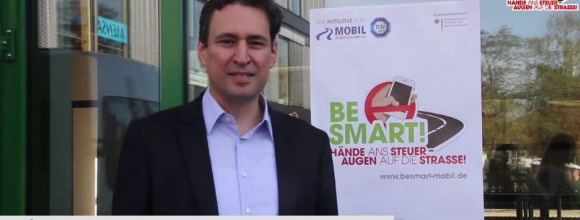 Ein Herr redet in eine Kamera mit BeSmart Plakat