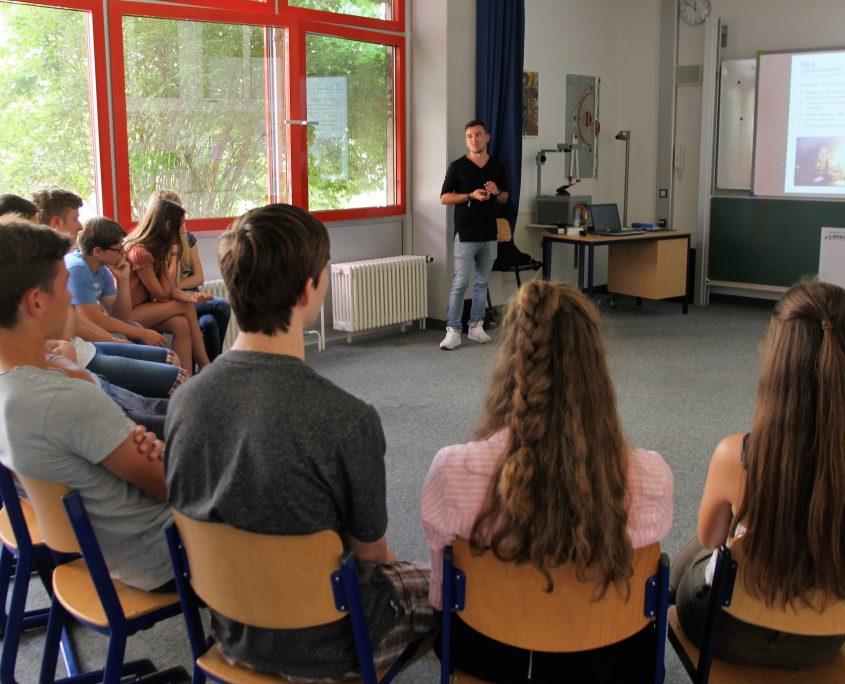 Junger Mann hält Vortrag vor einigen Schülern