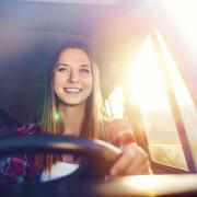 Mädchen lächelnd am Steuer eines Autos