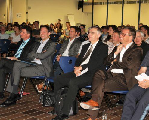 Publikum auf Stühlen lachen zu einem Vortrag der BeSmart Kampagne