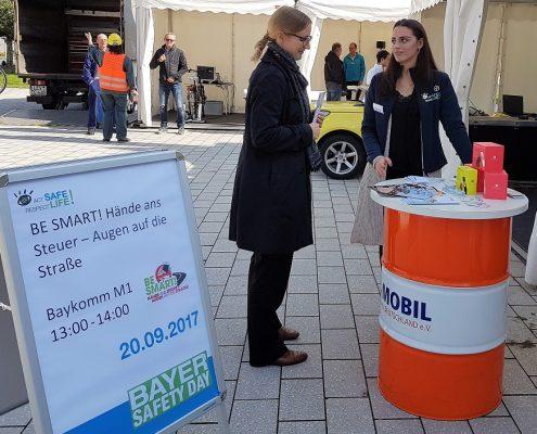 Zwei Frauen stehen vor einem Mobil-Stehtisch und reden